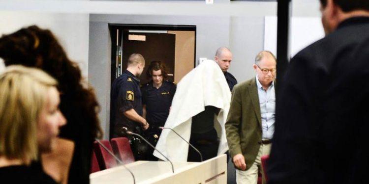 Anklagad går in i rättssal